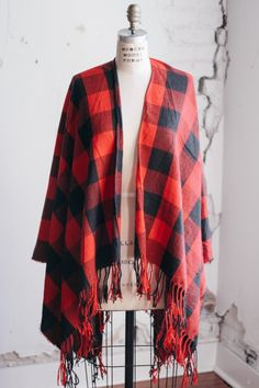 Cozy up with the new Red and Black Oversized Plaid Blanket Scarf by Bourbon & Boots. This red & black checkered poncho style features an open front, no closures and a fringe hem. This is a beautiful l