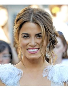 Steal Nikki Reed's elegant updo by first using a curling iron to create soft curls throughout your hair. Part your hair down the center and pull it back into a low and loose ponytail, allowing a shorter strands to fall free around your face. Gather a few curls at a time and pin them around the base of the pony tail, until all your hair is pulled back. Finish the look with a veil of lightweight hairspray.