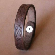 Made of top quality leather dyed a lovely dark brown color, with a hand-tooled design and a single polished nickel snap. The band is 5/8 inches wide. This band fits up to 8 1/2 wrists. If you would like this item in a different size, width, primary color,secondary color (if applicable),