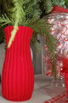 Cut the sleeves off thrift store sweaters to cover vases for a festive, cozy Christmas floral arrangement.