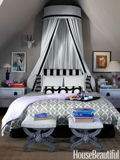 A king-size bed crowned with a dramatic canopy and contrasting black-and-white fabrics for graphic impact.