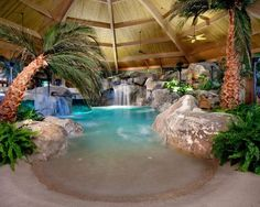 #Tropical landscape indoor #pool #design comes complete with a #beach and #waterfall. Gorgeous!