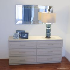 """The Ikea Malm dresser was transformed with 3/4"""" panel molding and brushing nickel drawer pulls. A large landscape mirror reflects light from the opposite window and helps brighten the room 