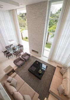 Sala de estar com pé direito duplo, lareira e em tons pastéis.