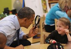 President Obama looks through a magnifying glass while visiting a classroom in Decatur, Ga.