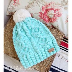 Knitted hat in teal cables with cream pom pom