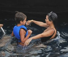 Swim time: Mason wore a bright blue life vest as he joined Kourtney in the water