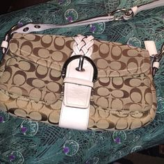 🎈🎉REDUCED 🎉🎈Coach Khaki signature handbag This is a authentic coach handbag in the khaki and tan signature print with white leather accents. It is in great condition and the leather is in perfect shape. There are no marks inside or out. It's a clean handbag with no signs of wear. Super cute handle that has silver hardware with white leather. A great started handbag or an everyday bag for the person who doesn't carry a large handbag. 🦄❤️please make an offer! I need to sell it all!🦄…