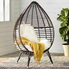 Craft a bohemian-inspired den seating group with this eye-catching chair, featuring an openwork teardrop design and a tufted white cushion. Top it with a pair of patterned pillows for a splash of style, then add woven poufs and lush potted succulents around the room to effortlessly complete the look.