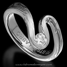 Nalu mokume gane diamond ring is crafted using Palladium White Gold and Sterling Silver with an excellent cut diamond. A modern mokume gane ring with an harmonious shape.
