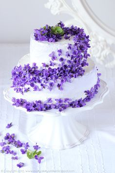 Beautiful white tiered cake, with violets.