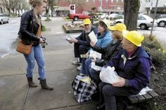 """Friends of the Corvallis-Benton County Public Library organized a """"book flash mob."""" Participants wore a yellow hat, gathered at an assigned location at an assigned time and started reading. When a passerby asked one of the yellow-hatted readers what was going on, the reader would hand their book to that person. Each participant had brought a book to the event that was meaningful or had inspired them. Inside the book was a flyer asking the new owner of the book to do the same after reading it."""