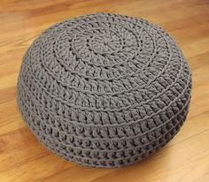The homey comfort of T-shirt material teams up with crochet home decor to bring you the Comfy Crochet Pouf DIY. The thickness of the yarn makes this pattern look like woven twists, and it& the perfect size for an ottoman or a floor pillow. Crochet Pouf Pattern, Diy Tricot Crochet, Crochet Cushions, Crochet Pillow, Crochet Hooks, Diy Crochet Floor Pouf, Crochet Rugs, Easy Crochet, Crochet Home Decor