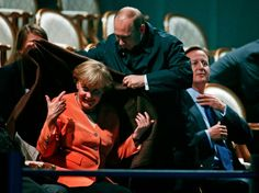 #Russia Vladimir Putin and Angela Merkel at the G20 summit. Russian President Vladimir Putin covers Germany's Chancellor Angela Merkel warm blanket as they arrived for the Water and Music Show during the G20 summit at Peterhof Palace in St. Petersburg, on September 6, 2013. British Prime Minister David Cameron is on the right.