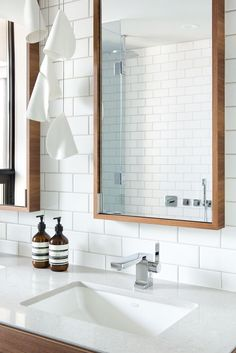 Falken Reynolds - Vancouver loft ensuite bathroom with walnut double vanity with Caesarstone counters, framed recessed medicine cabinets, white subway tile walls and Mutina Ceramics black Tex tiled floors photo by Ema Peter