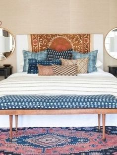 The white headboard, bedding, lampshades, and ceiling in this bedroom provide a clean, modern base for such international elements as shibori pillows, a batik tapestry, and a kilim rug. The blue hues keep everything unified and counterbalances the warm tones of the jute, mudcloth, wood, and walls.