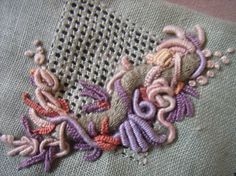 These bullions are worked on a pulled thread background using the Casalguidi style of embroidery. The very long knoted bullions are about an inch or so long. They are over a raised stem band