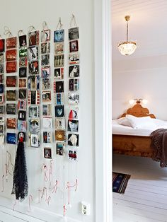 love this idea of displaying photographs by hanging them, it's less work cause you can hang them from a single tack or screw, hook, knob, whatever... and it looks really nice