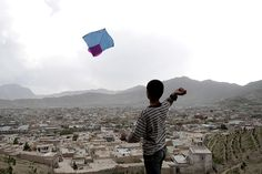 Kabul, Afghanistan: A boy flies a kite from the top of one of the mountains surrounding the Afghan capital