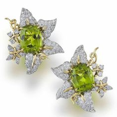 A voluptuous pair of peridot and diamond earclips by Valentin Magro. Each designed as pavé-set round brilliant-cut diamond blossom with curling tendrils centering a cushion-cut peridot, estimated total peridot weight: 22.25 carats, estimated total diamond weight: 4.57 carats; mounted in platinum and eighteen karat gold. #eargasm #peridotpassion