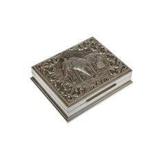 A Siam sterling silver cigarette box, the rectangular hinged lid repousse with a mounted elephant at work, the spandrels embellished with scrollwork, engraved with a presentation inscription to the base, stamped SIAM STERLING. 13cm by 11cm.