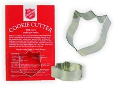 """Salvation Army Shield cookie cutter.  These lovely cookie cutters are handmade for us here in Virginia, and they are just neat! Hand-shaped in sturdy tin, they'll cut more cookies than you could ever imagine baking.  Each card includes a favorite recipe for sugar cookies. The cutter and card are neatly packaged in a clear cello bag. The card is 5½"""" x 8½"""", and the cutter is 3"""" x 2½"""" x 1"""" high."""