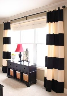 Bold black and white stripe curtains complement the dark wood unit with lighter rattan boxes. Make a great statement in an otherwise neutral room.