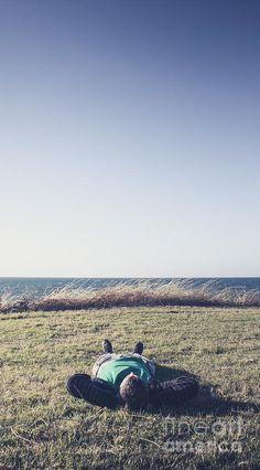 Lifestyle portrait of a resting young man lying down on a grass field by the ocean. Taken Devonport, Tasmania, Australia by Ryan Jorgensen