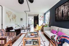 Sala de estar tem parede pintada de cinza e móveis menores e acessórios com pontos de cores.