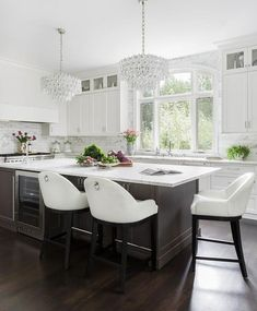 Three white upholstered counter stools sit at a brown oak island fitted with a glass front wine fridge and topped with a honed white marble countertop lit by Aerin Liscia Chandeliers.