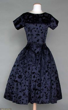 "TRAINA-NORELL MIDNIGHT BLUE PARTY DRESS, c. 1955 Silk velvet floral pattern cut to silk satin, long fitted bodice to CF & CB waist point, self covered back buttons, stiffened crinoline, narrow belt, label, B 34"", W 26"", L 44"", excellent. Brooklyn Museum"
