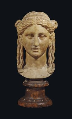 A ROMAN MARBLE HEAD OF A YOUNG WOMAN -  CIRCA 2ND CENTURY A.D.