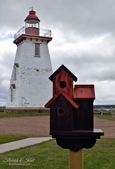 A red birdhouse in front of the historic lighthouse in Souris, PEI Country Scenes, House Paint Exterior, Green Fields, Prince Edward Island, Vacation Destinations, House Painting, Bird Houses, Lighthouse, Sky