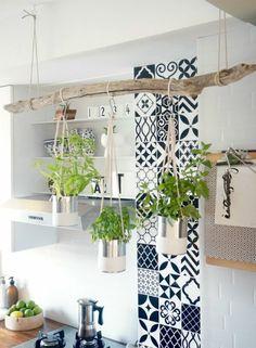 une solution pour habiller un mur en mosaïque de faïence, bleu et blanc, colonne décorative près du lavabo et du plan de travail, décoration avec une pièce en bois grise tenue par des cordes sur laquelle on a suspendu trois pots blancs avec des plantes vertes