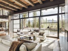 10: A Contemporary Neutral Living Room in Truckee, CA  A gray leather chair, paired with its matching ottoman—both by Minotti from Arkitektura—swivels to take advantage of conversation in the living area or views through the sliding doors toward the terrace.