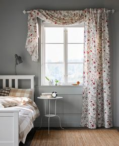 A floral-printed curtain hangs in a window in a bedroom.