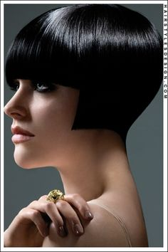 Hair Style: This is a cool looking hairstyle as this woman seems to have two different styled going on. The hair is straight and short for this look. At front, straight bangs come down thick onto the forehead. At the sides, the hair is cut straight across with the hair at back cut into a point. The overall look for this is stylish.  Hair Cut: This haircut is short.  Hair Colour: The hair colouring is black.