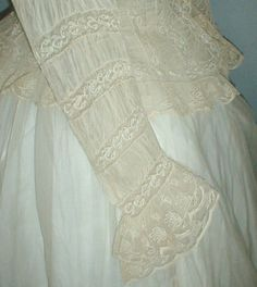 """1860s white organdy dress two piece summer dress.  Bodice has rows of ruching and inserts of Val lace, unlined with front button closure.  Armscyes and shoulders are piped.  Neckline, front opening & sleeve cuffs trimmed with lace.  Skirt hemline is trimmed with ruching and inserts of lace & is unlined.  Bust: 34""""; Waist: 24"""", Front skirt length: 37-1/2""""; back skirt length: 46""""; width at hemline: 130""""."""