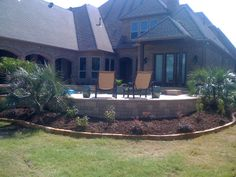 GroundScape, a Fort Worth Landscape Company, installs landscape around the back of a pool.