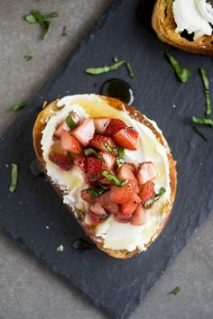 Easy Strawberry Crostini - This delicious strawberry crostini recipe is perfect for summer entertaining! Creamy goat cheese and a simple strawberry salsa with fresh basil and balsamic are layered on crispy french bread and topped with a drizzle of honey. Vegetarian.
