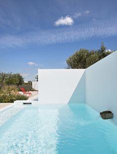Une piscine qui joue avec le soleil. Le bassin de nage s'étire le long du mur qui sépare le jardin d'agrément du grand potager et des champs alentours.