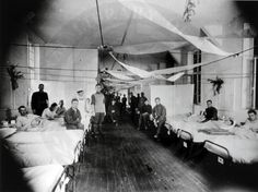"""Black and white photo of rows of beds. Patients sit on the beds. """"An old cliche maintained that influenza was a wonderful disease as it killed no one but provided doctors with lots patients. The 1918 pandemic turned this saying on its head."""""""
