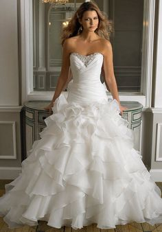 This drop waist organza fit and flare features alternating and cascading ruffles. The sweetheart neckline features silver embroidery, pearls, and beading.