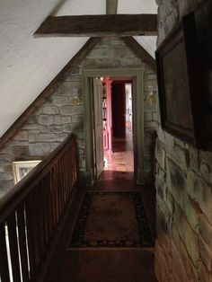 The breezeway is a bridge/passageway that connects the bedroom on top of the garage with the main house/library. The stone wall marks the exterior wall of the house. The breezeway, the stone turret stair, bedroom and garage were later additions to the original home. The house was expanded and altered three times.