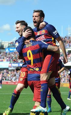 Luis Suarez of Barcelona celebrates scoring his team's first goal with his team mates Jordi Alba and Lionel Messi during the La Liga match between Granada and Barcelona at Estadio Nuevo Los Carmenes on May 14, 2016 in Granada, Spain.