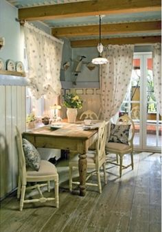 One of the loveliest country-style dining rooms we've seen in a while. Painting walls and ceiling in pale grey/blue gives a modern feel to the scheme but with natural, distressed wood flooring, pretty window treatments and painted furniture, there is an eclectic but charming country flavour.