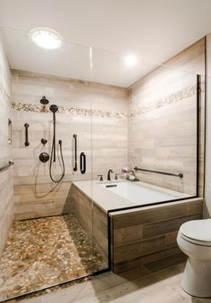 This master bath remodel features a beautiful corner tub inside a walk-in shower. The side of the tub also doubles as a shower bench and has access to multiple grab bars for easy accessibility and an aging in place lifestyle. With beautiful wood grain por Master Bathroom Shower, Small Bathroom With Shower, Shower Tub, Modern Bathroom, Bathroom Ideas, Bathroom Gray, Shower Ideas, Bathroom Showers, Bath Ideas
