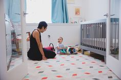 A photojournalistic photograph of a mother playing with her baby in his room during an in home family photo session in Jamaica Plain - Boston, Massachusetts - Gina Brocker Photography