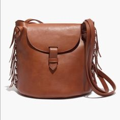 """Madewell Natural Leather Fringe Bucket Bag In smooth, soft leather, this slouchy bucket bag is just the right size for all your essentials. Trimmed with hand-knotted fringe, it has that slightly vintage look that's made for warm-weather adventures. Worn only a handful of times - some natural variations in the leather. •Leather. •Tab closure. •Interior pocket. •15 7/10"""" handle drop. •9 1/2""""H x 9 1/2""""W X 7""""D. •Import. Madewell Bags Crossbody Bags"""