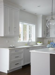 White and gray kitchen features a clear glass globe pendant illuminating a center island painted light gray topped with honed white marble.